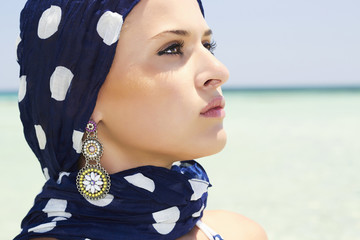 beautiful woman in a blue scarf on the beach