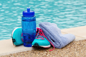 Water bottle by pool. Exercise and hydration concept.