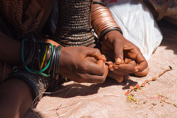 Himba woman making jewelry