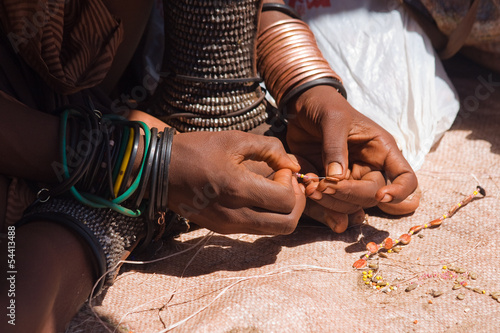 Himba woman making jewelry