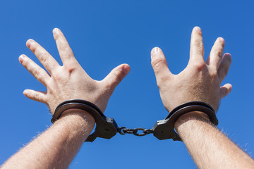 closeup of the hands of a man with handcuffs on a blue backgroun