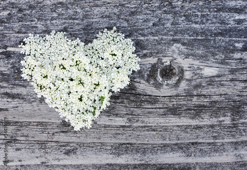 Heart from flowers on old wooden background