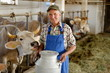 Farmer is working on the organic farm with dairy cows - 54416073