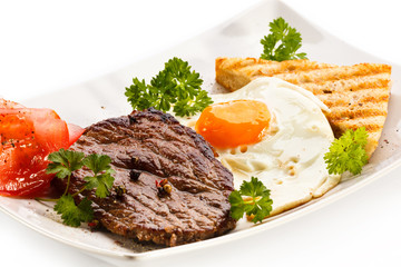 Grilled steak, toast, fried egg and vegetables