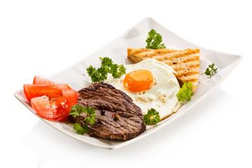 Grilled steaks, toast, fried egg and vegetables
