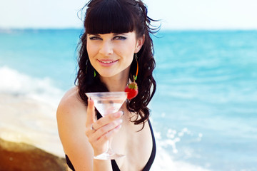 Beautiful girl on beach with cocktail