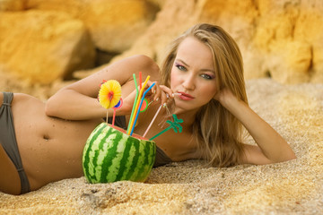 The girl eats water-melon on beach