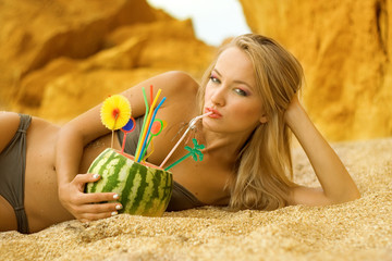 The girl eats water-melon on beach