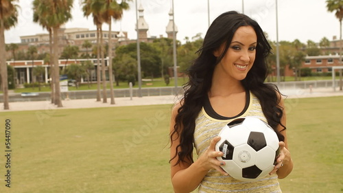 Sexy happy football woman with ball towards camera