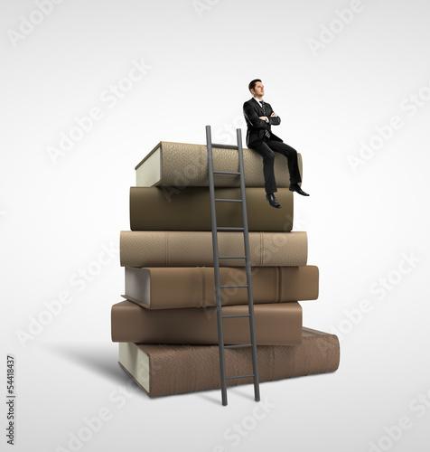 businessman sitting on books