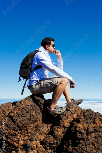 Young Man Having a Rest in a High Peak Over Clouds in Teide Moun