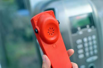 Mano tiene una cornetta rossa di un telefono   pubblico