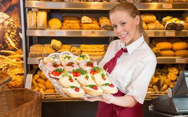 Verkäuferin in Bäckerei mit Tablett voller belegter Brötchen