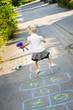 canvas print picture - Kleines blondes Mädchen spielt auf der Straße