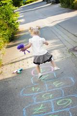 Kleines blondes Mädchen spielt auf der Straße