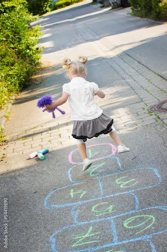 canvas print picture Kleines blondes Mädchen spielt auf der Straße