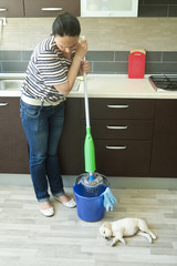 Angry woman squeezing mop near puppy