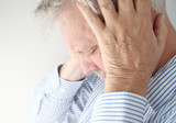 stressed older man holds his head in both hands
