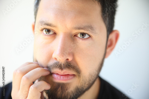 young man scratching his beard