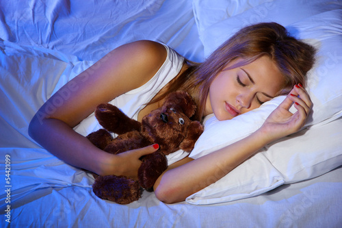 young beautiful woman with toy bear sleeping on bed in bedroom