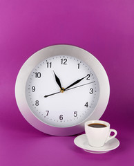 Cup coffee and clock on purple background