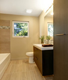 Beige modern new bathroom with brown wood cabinets and tub.