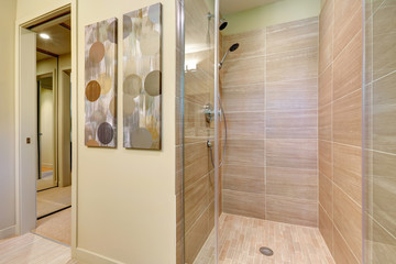 Bathroom shower with glass doors and natural color tiles.