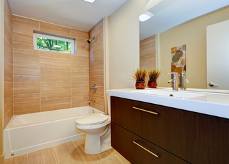 Modern new bathroom design with double sink and white tub.