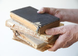 man holds several old, damaged books