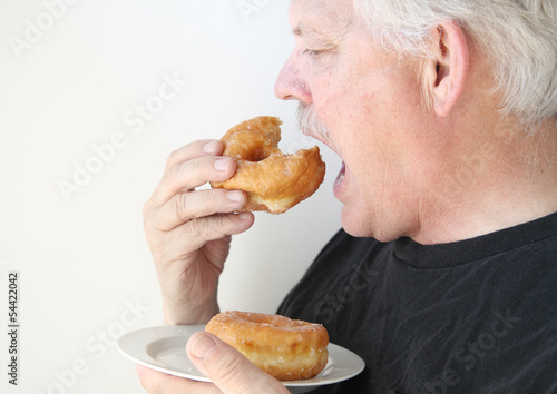 older man eats glazed doughnut