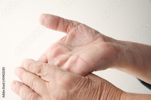 older man bends hand back