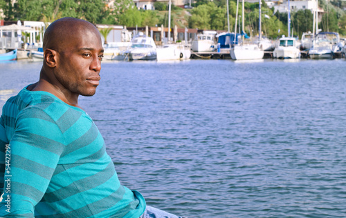 Black man enjoying the summer.Background with yachts