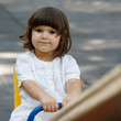 Cute little girl on swing in the playground