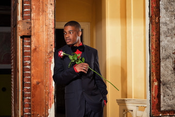 Vintage fashion afro american groom holding red rose. Standing i