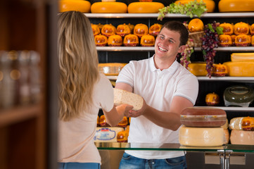 Male salesman in cheese store with a female customer