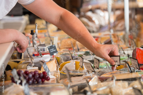 Unrecognizable male supermarket worker with cheese closeup