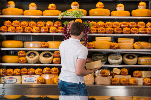 Handsome male owner of a cheese store working