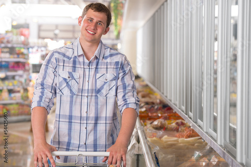 Young man shopping for frozen food in a grocery store