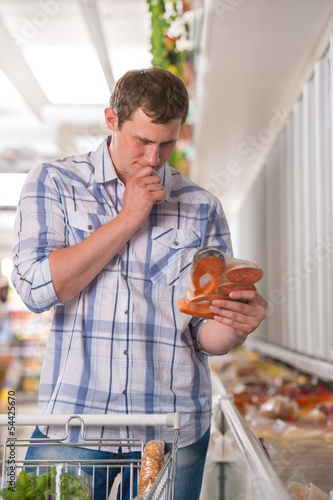 Man thinking about products at the supermarket