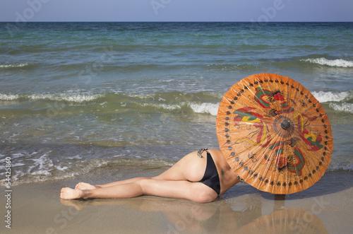 Modella sulla piaggia con ombrello