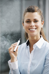 portrait of young woman smoking electronic cigarette outdoor off