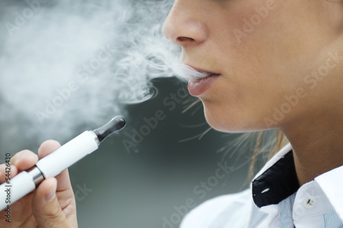closeup of woman smoking electronic cigarette outdoor - 54426430