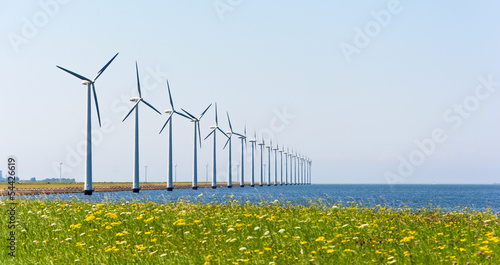 Wind energy windmills near grassland and sea shore
