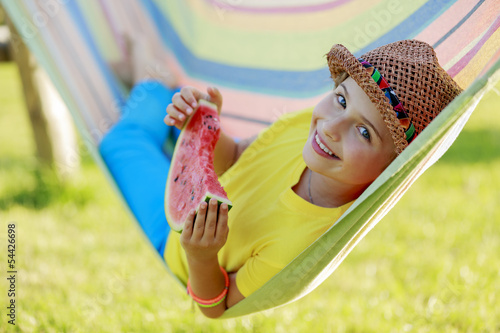 Summer joy - happy girl with  watermelon in hammock