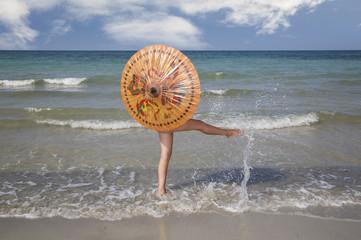 Modella sul bagnasciuga con ombrello cinese