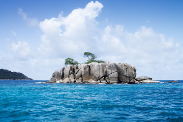 Blue sea and white cloud with green island. Seychelles