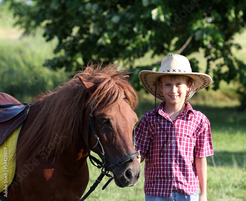 boy with cowboy hat and pony horse