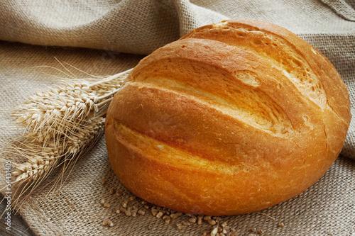 Fototapeta Fresh bread and ears of wheat