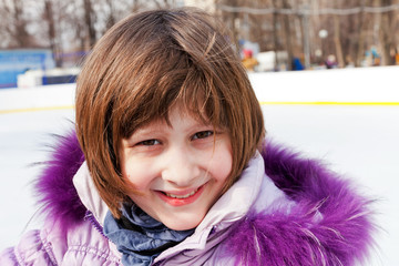 smiling girl on rink in sunny winter day