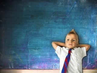 little schoolboy with blackboard in background